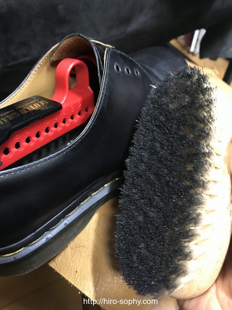 黒い革靴にクリームを塗る