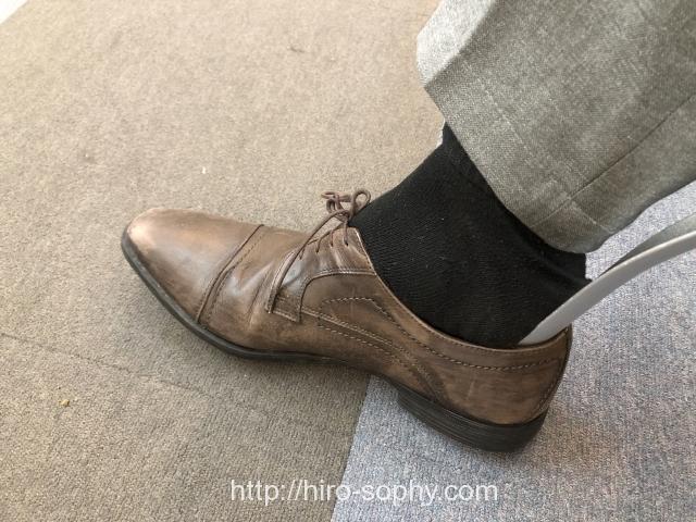 茶色の革靴を靴べらを使い履く