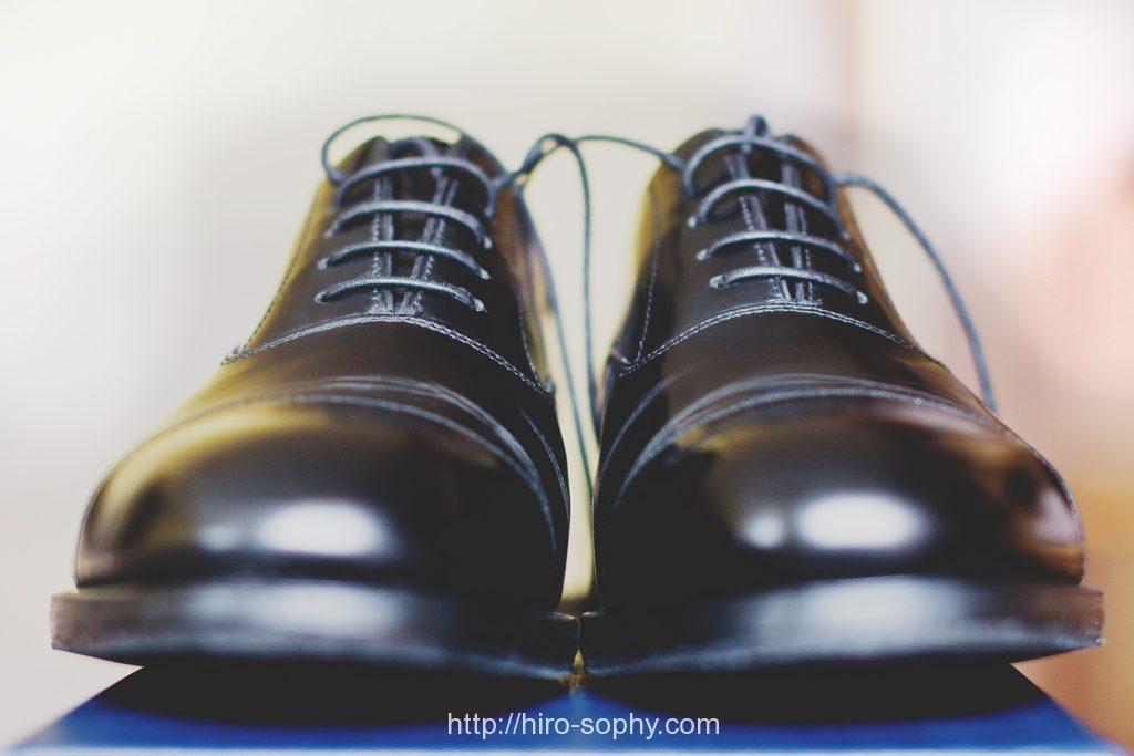 両足の紐が解けた黒い紳士靴