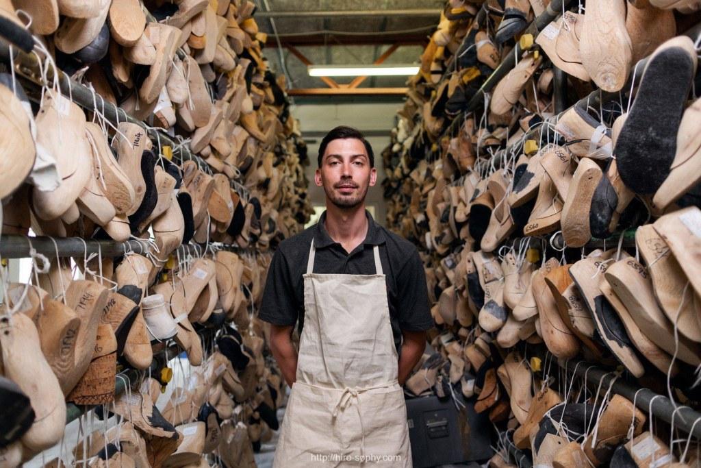 革靴のラストに囲まれる男
