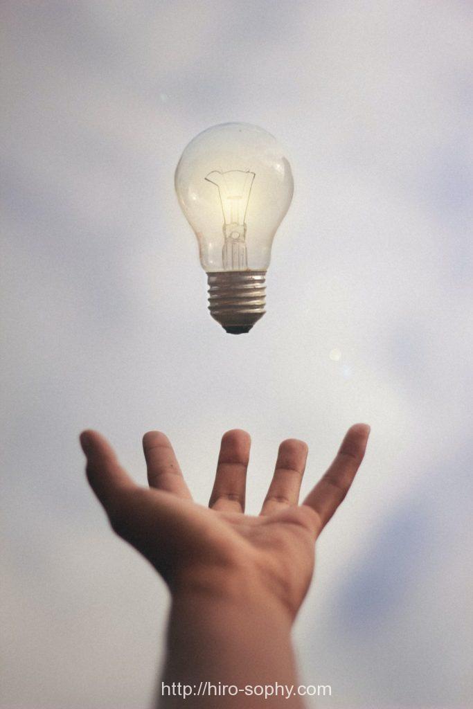 手の上に電球が浮かんでいる