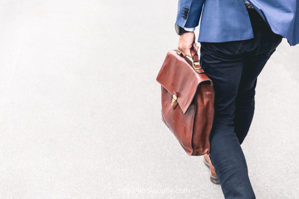 歩く茶色のカバンを持ったビジネスマン