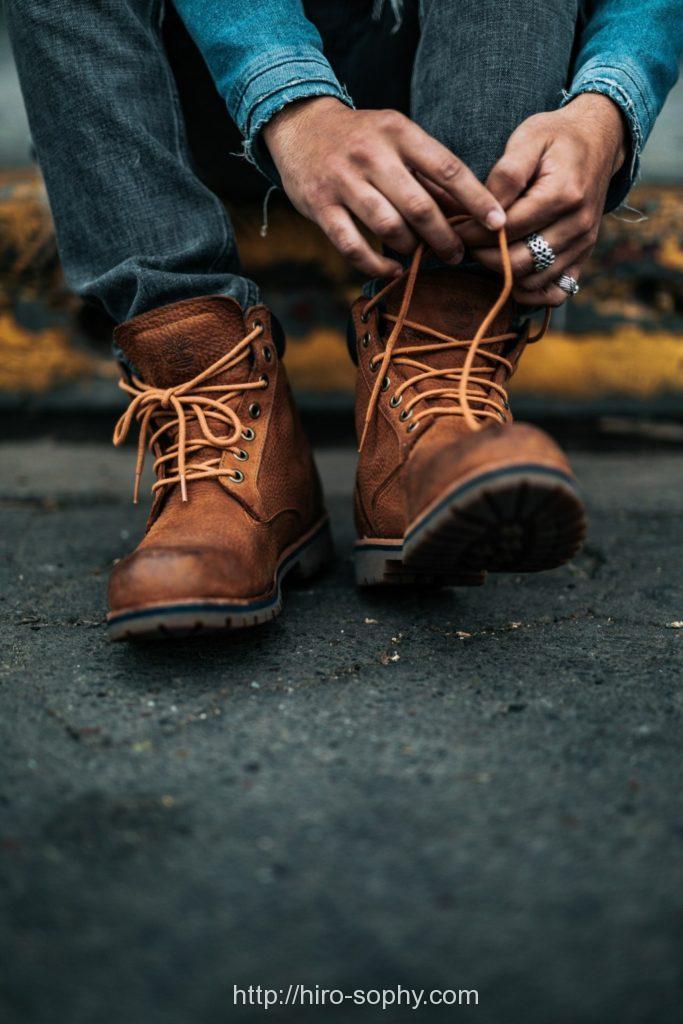 革靴の紐を締め直す