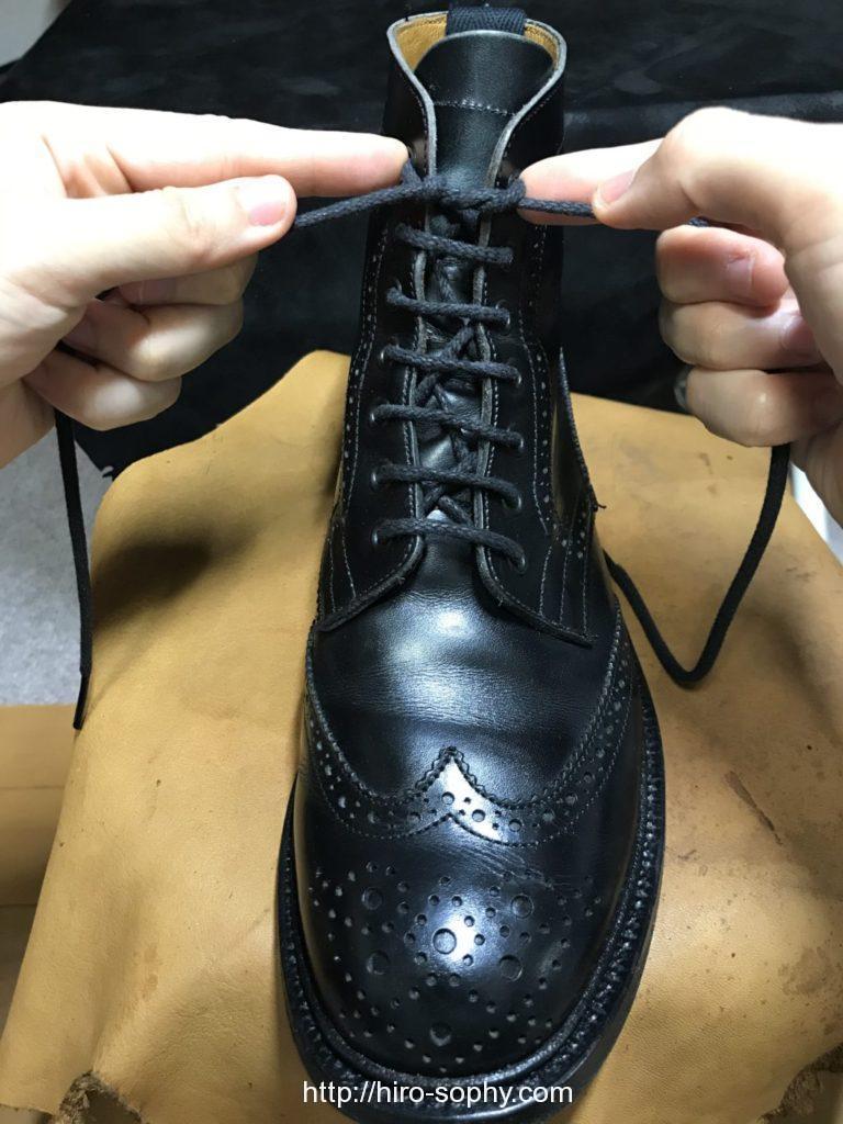 黒いブーツの紐を一重結びをする