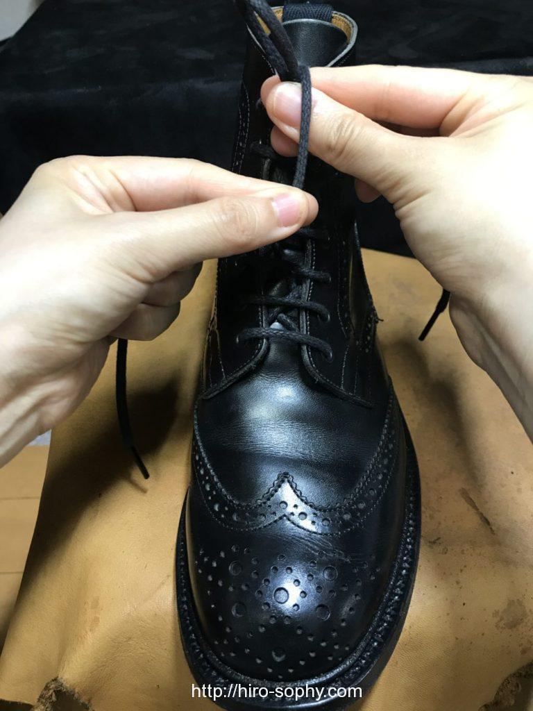 黒いブーツの紐をベルルッティで結ぶ