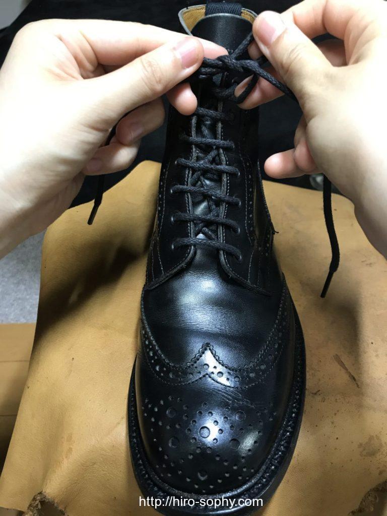 黒いブーツの紐をほどけないように結ぶ