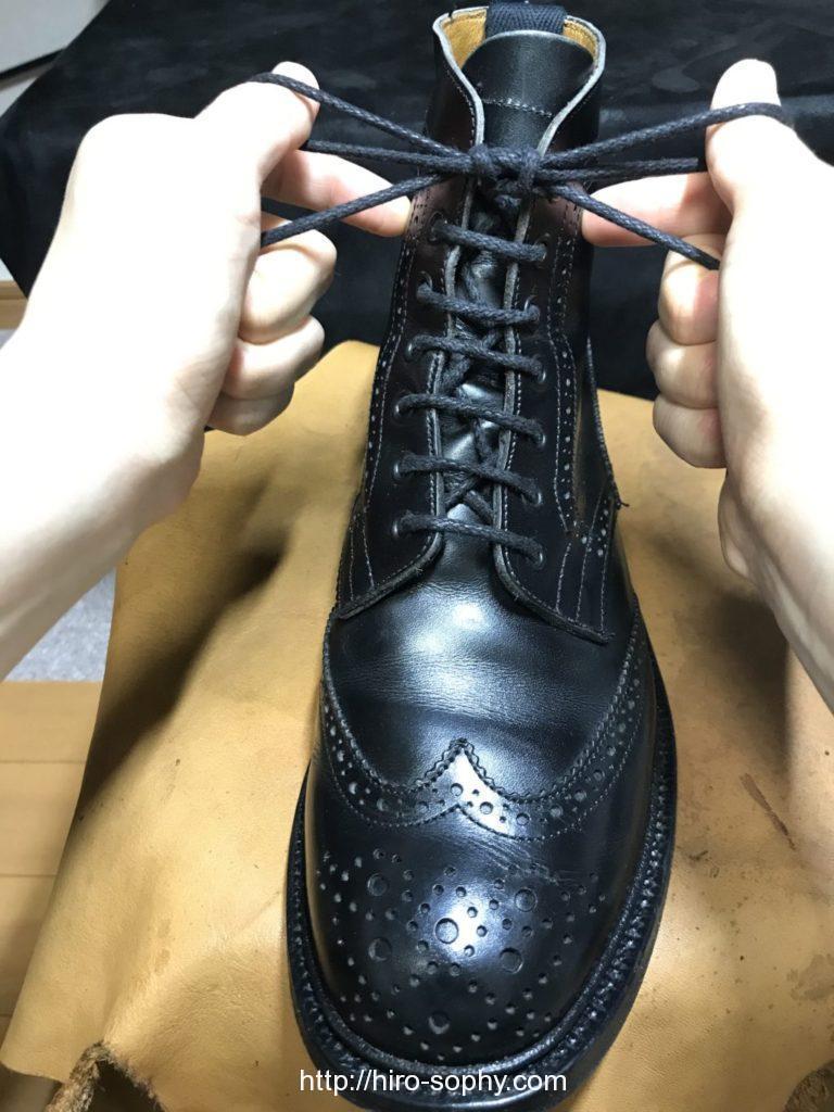 黒いブーツの紐をしっかりと締め直す
