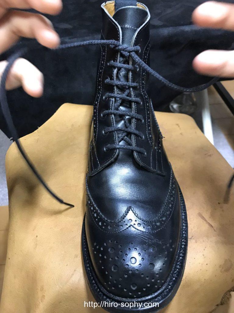 黒いブーツの紐を一重結びにし小指に紐をかける