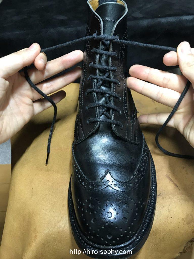 黒いブーツの紐を両手で左右に引く