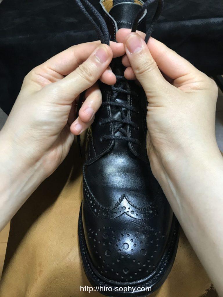 黒いブーツの紐を折り曲げ輪を作る
