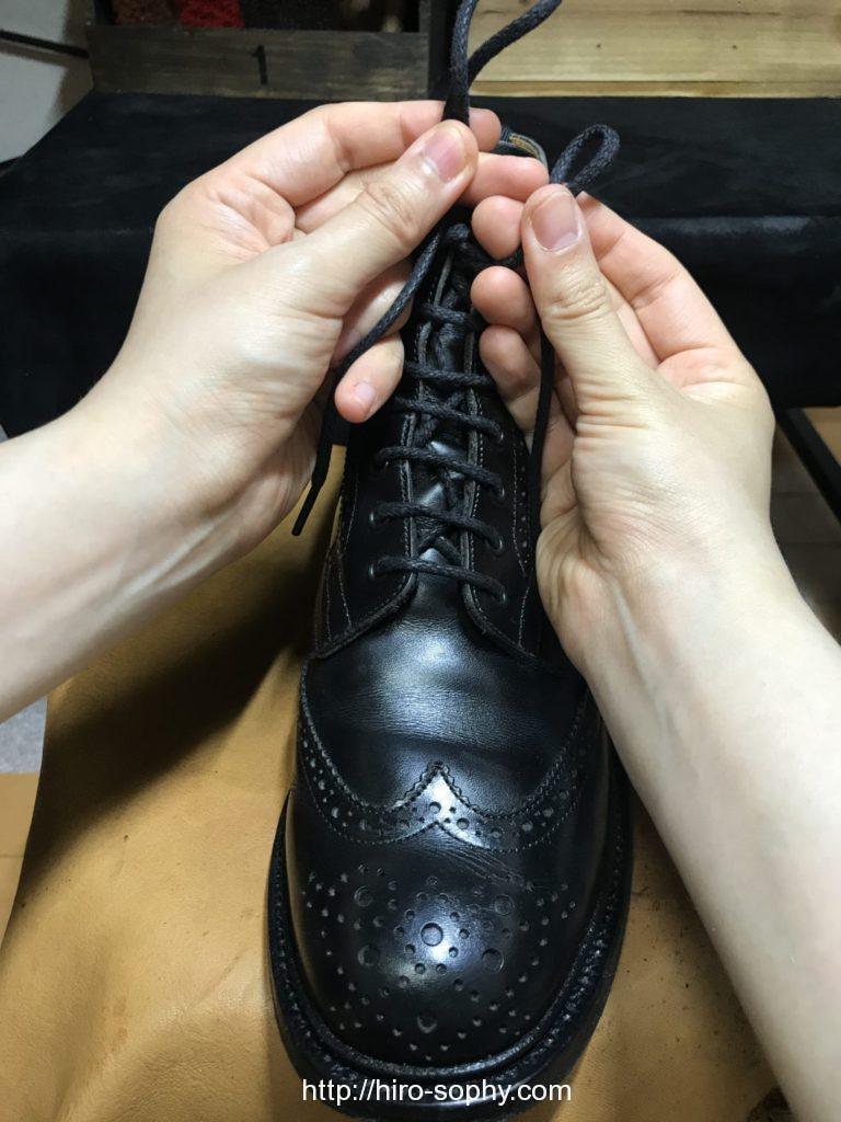 黒いブーツの紐の輪を交差させる