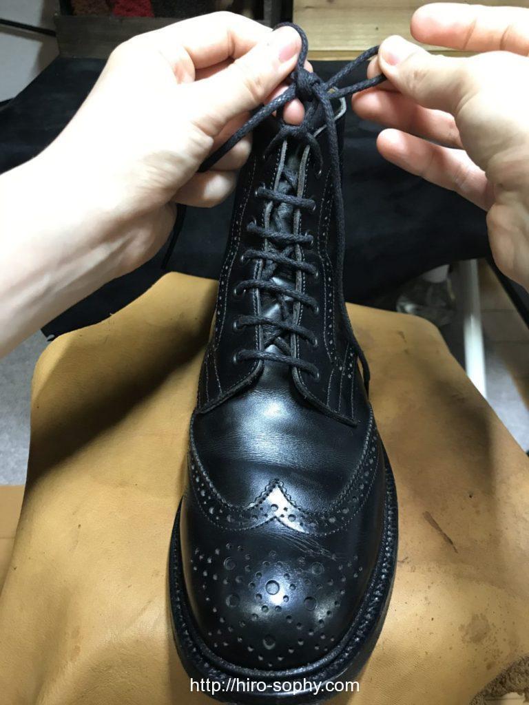 黒いブーツの紐を結ぶ
