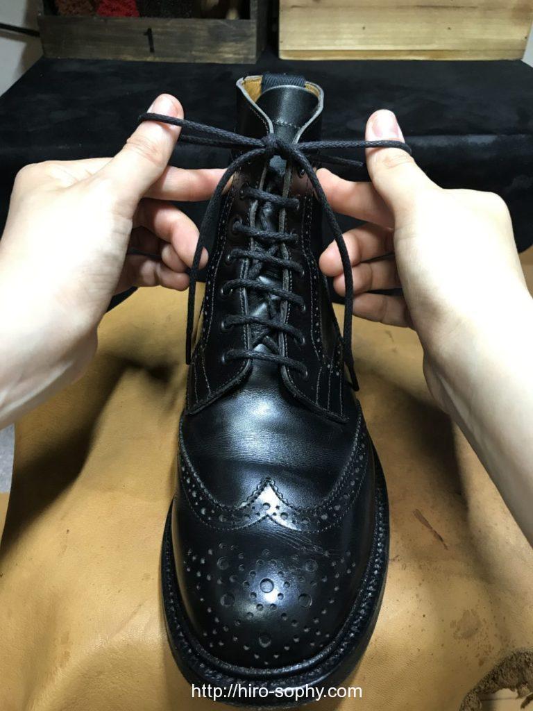 黒いブーツの紐の長さを整える