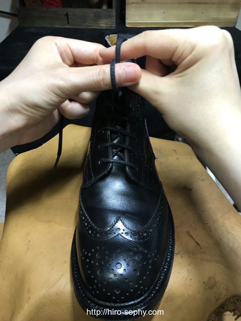 黒いブーツの紐を両手の指にかけ交差させる