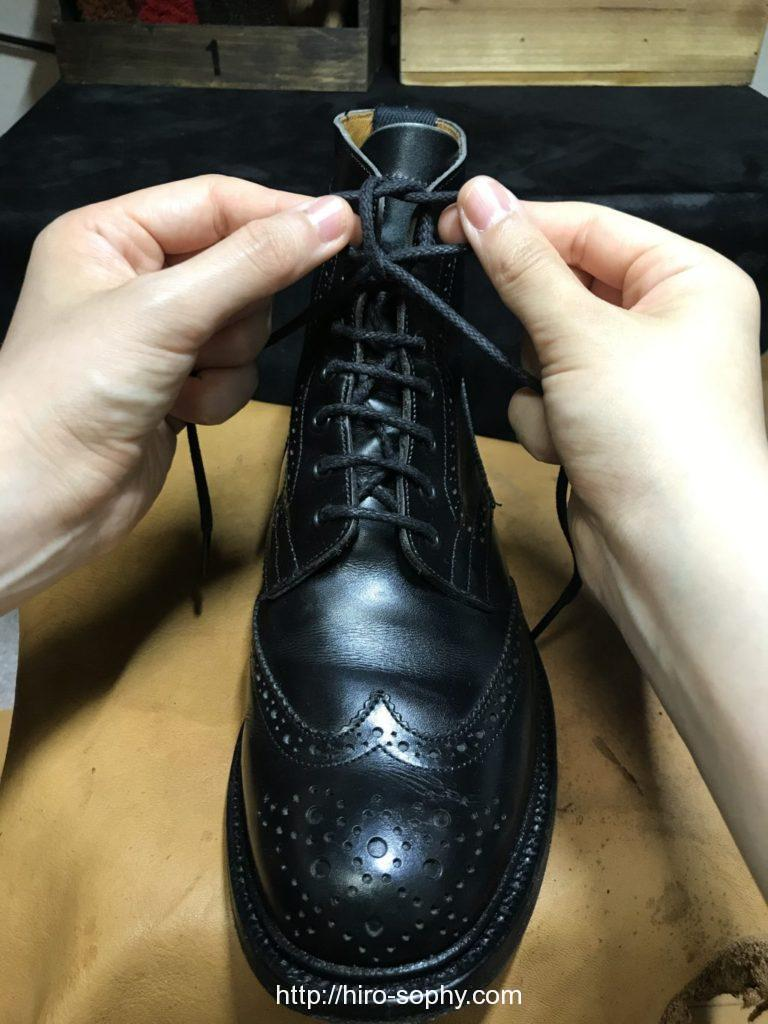 黒いブーツの紐を左右に引き締める