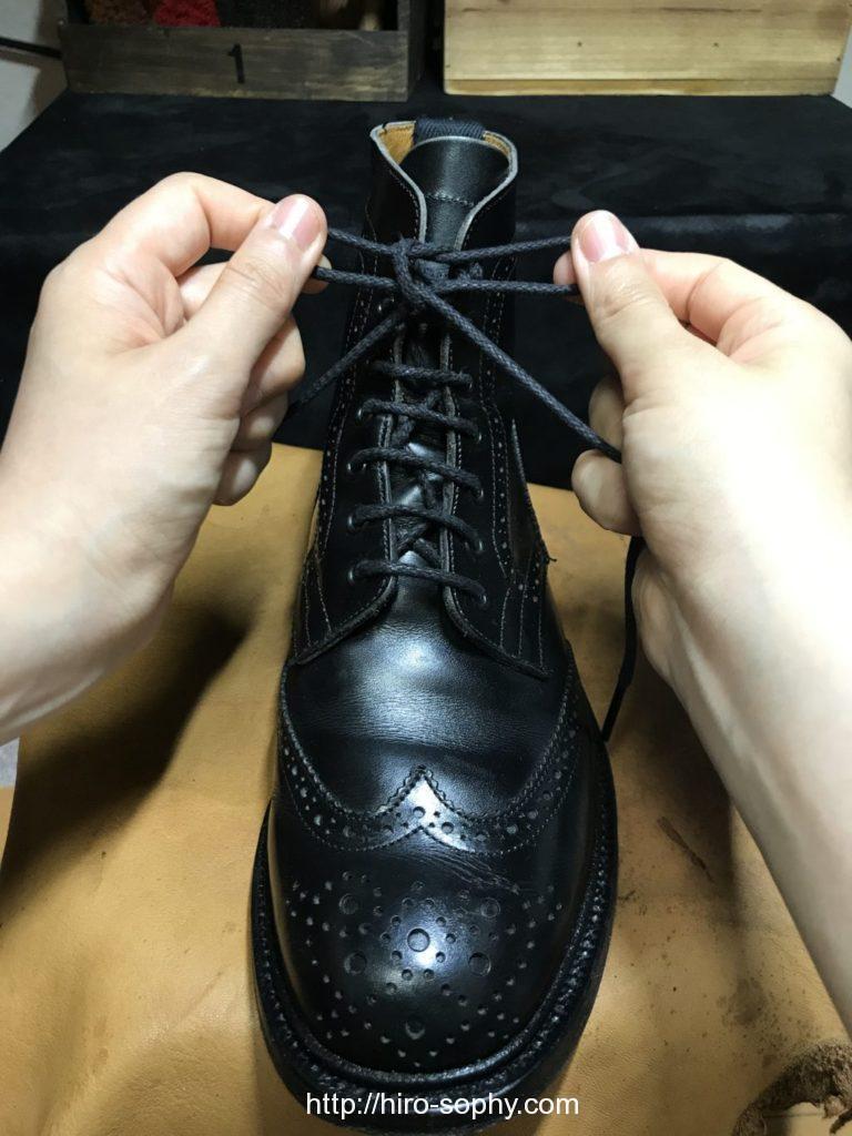 黒いブーツの紐を両手を使いしっかり締める