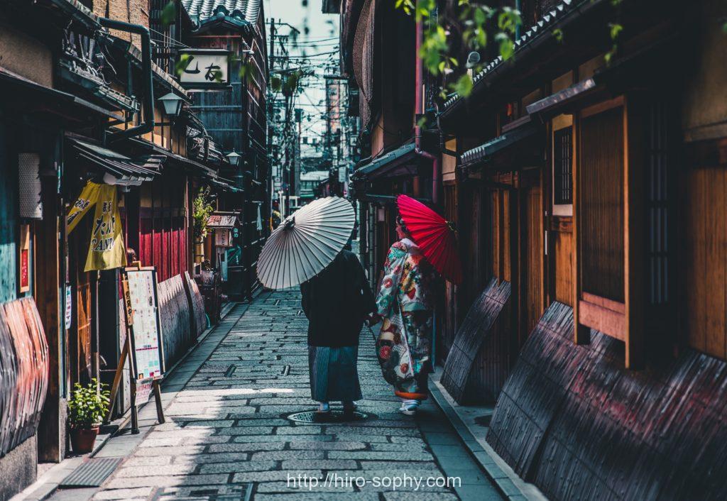 着物を着た男女が傘を差して歩く