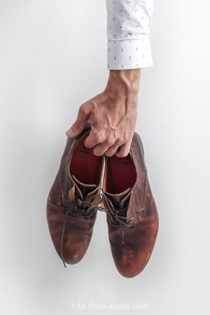 ボロボロの靴を片手に持っている