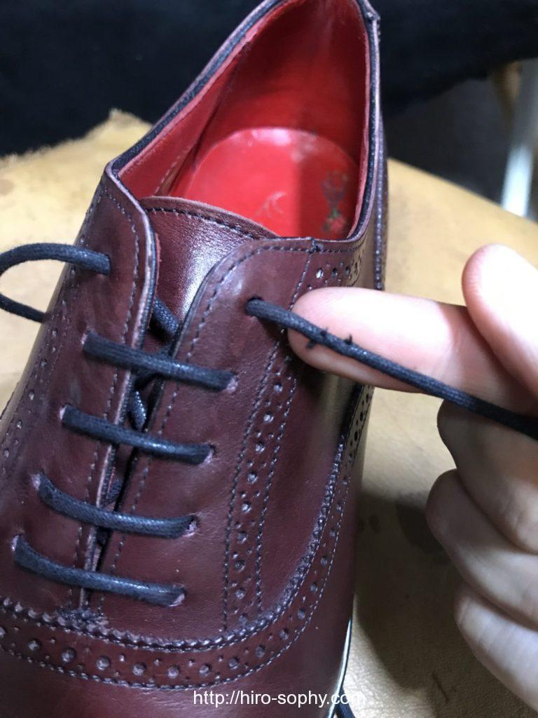 靴紐が切れかかった状態の革靴