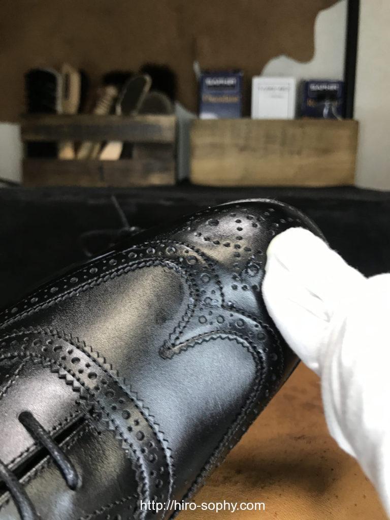 黒い革靴にクリームを塗布する