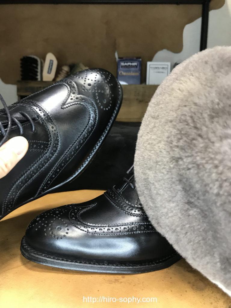 黒い革靴をミトンで乾拭き