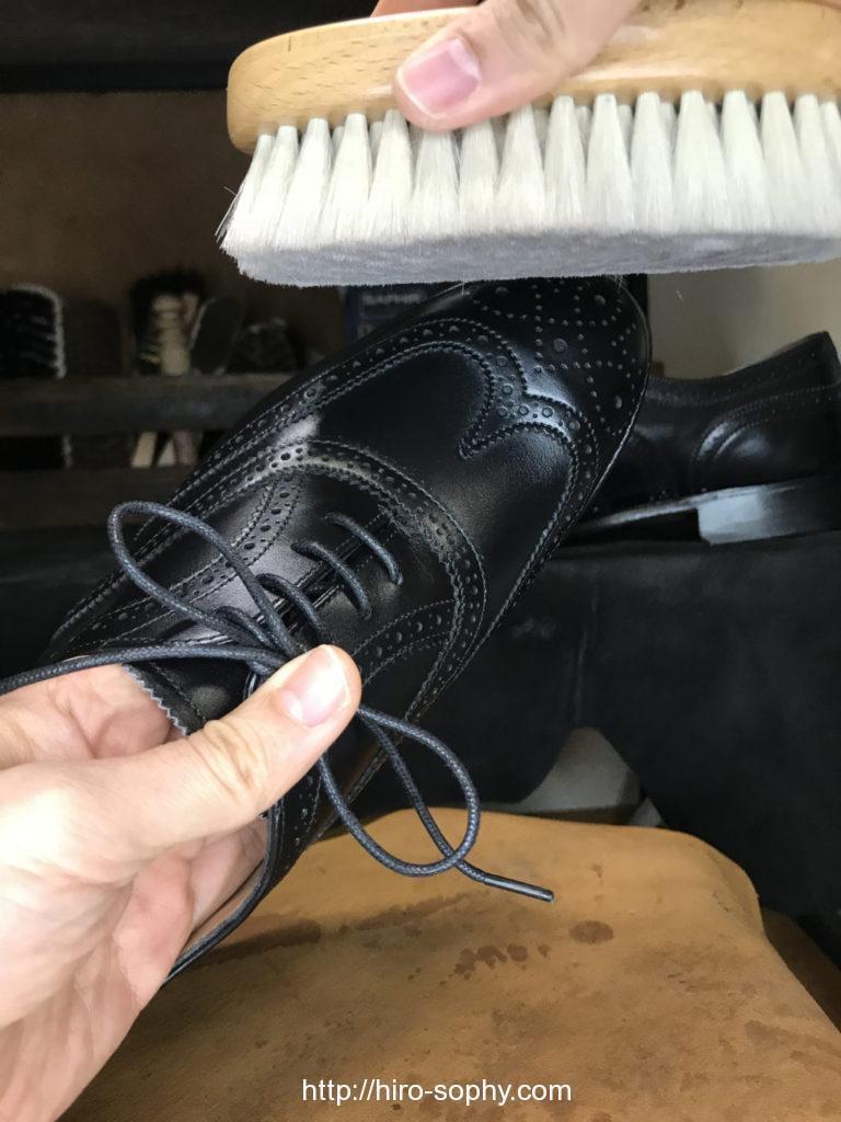 黒い革靴を仕上げブラシでブラッシング