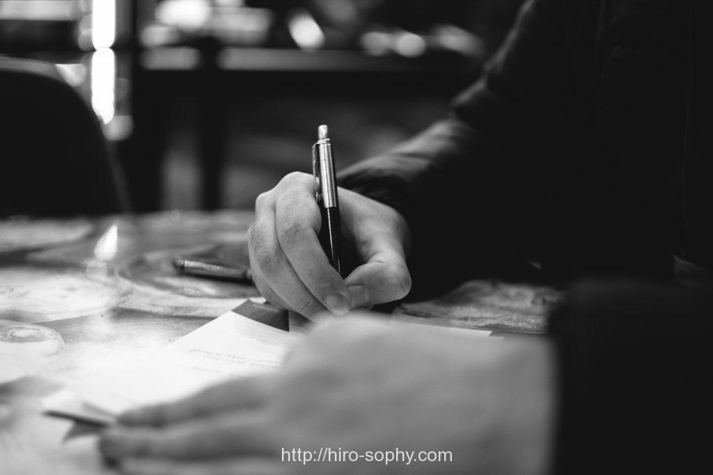 ボールペンで字を書く男の手