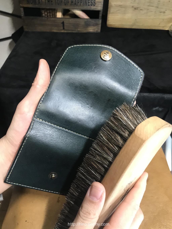 艶出しクリームを塗った革財布をブラッシング