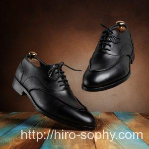 Uチップの黒い革靴